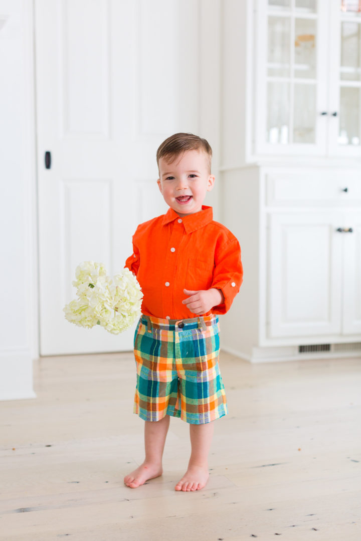 Eva Amurri Martino's son Major wears a pair of colorful green plaid shorts and an orange button up shirt while holding a handful of hydrangeas.