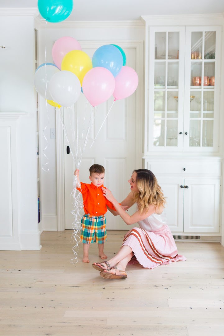 Eva Amurri Martino plays with her son Major while holding a handful of colorful balloons
