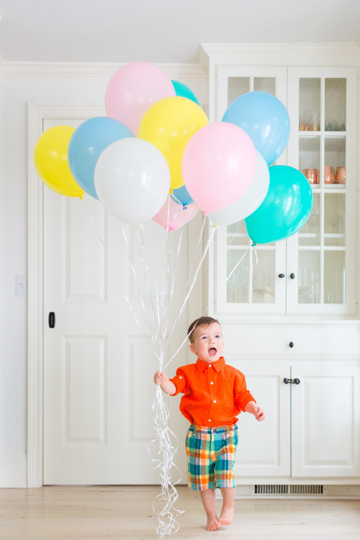 Eva Amurri Martino's son Major wears a colorful outfit while holding a handful of multicolored balloons in their Connecticut home.