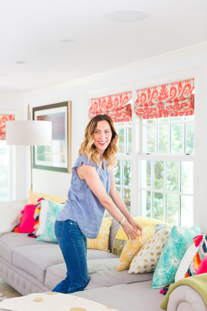 Eva Amurri Martino fluffs a colorful selection of pillows on her couch at her home in Connecticut