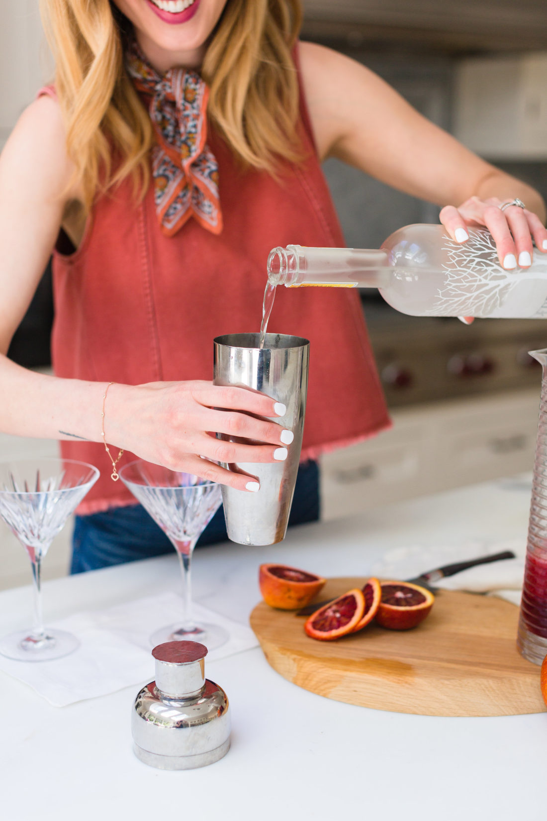 Eva Amurri Martino pours vodka in to a cocktail shaker to make blood orange and ginger martinis