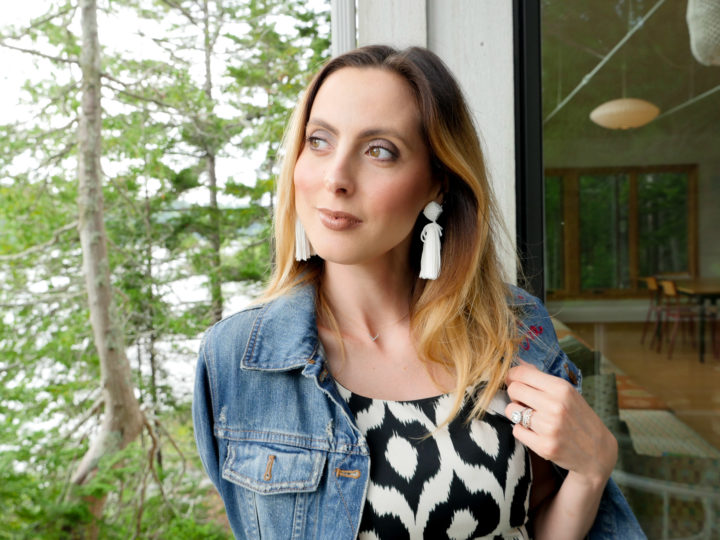 Eva Amurri Martino wears a geometric printed dress with a flare of pink and a denim jacket and white tassel earrings in Bar Harbor, ME.