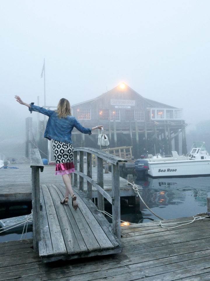 Eva Amurri Martino wears a geometric printed dress with a flare of pink and a denim jacket in Bar Harbor, ME.