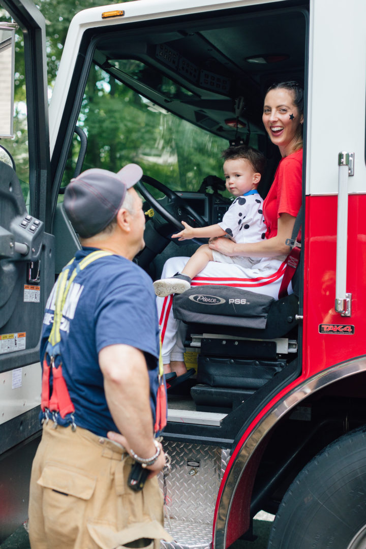 Eva Amurri Martino sitting in a firetruck with son Major at her daughter Marlowe's 4th birthday party