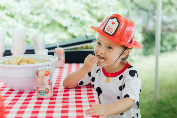 Eva Amurri Martino's daughter Marlowe eating chips at her 4th birthday party in a fireman hat