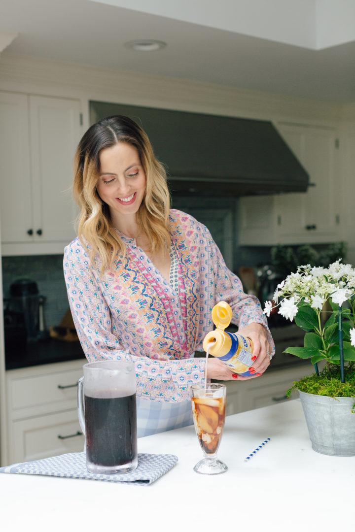 Eva Amurri Martino pours International Delight coffee creamer into an iced coffee