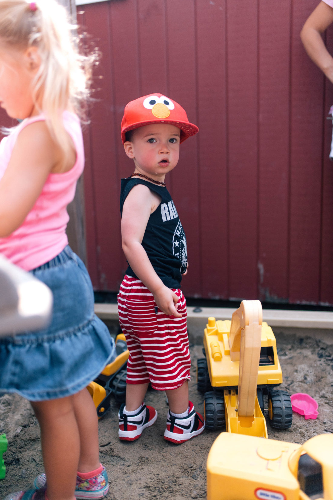 Major Martino stands in the sand box in Connecticut, wearing striped shorts and an elmo hat