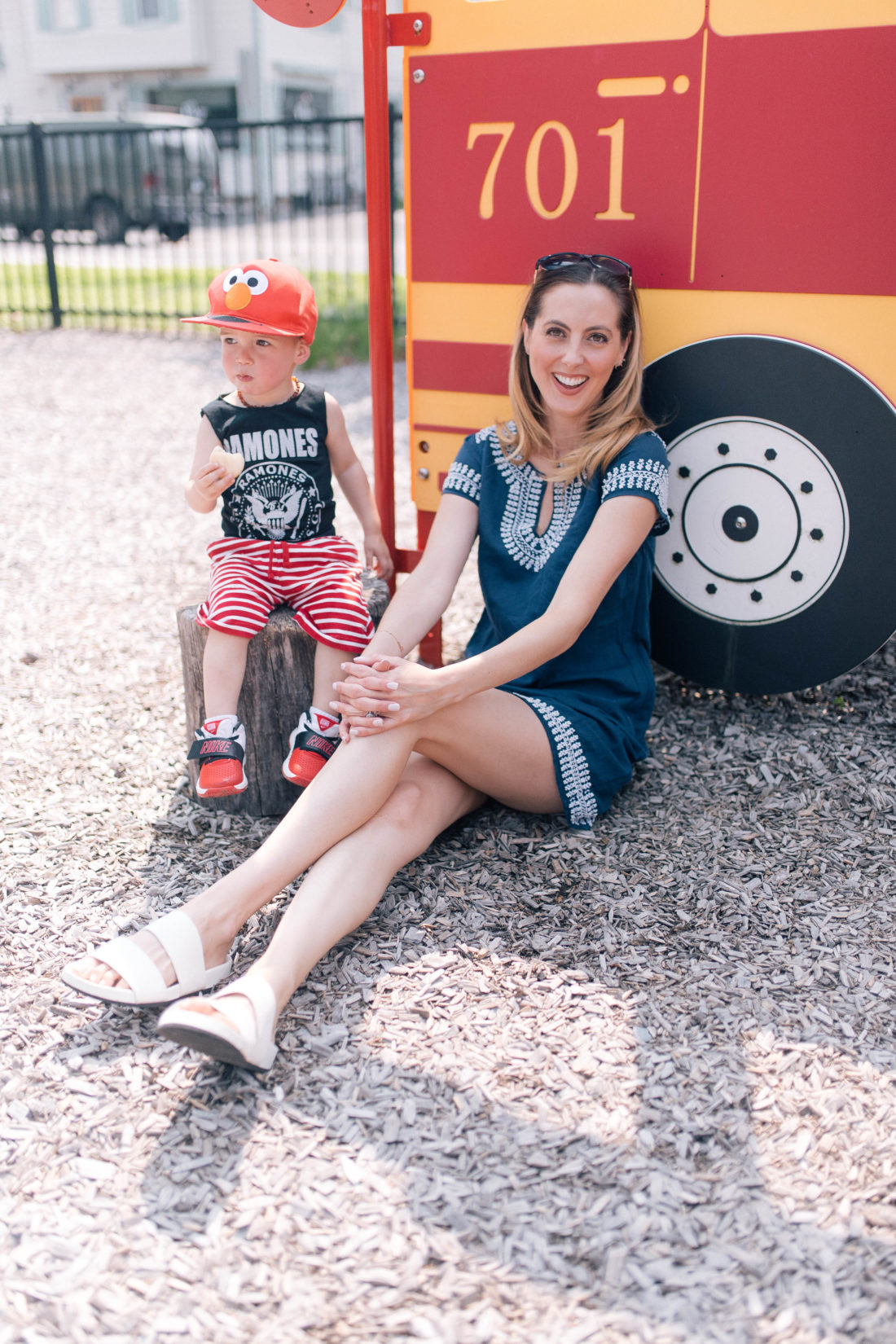 Eva Amurri Martino sits on the ground wearing a navy blue dress, while son Major snacks on a stool next to her