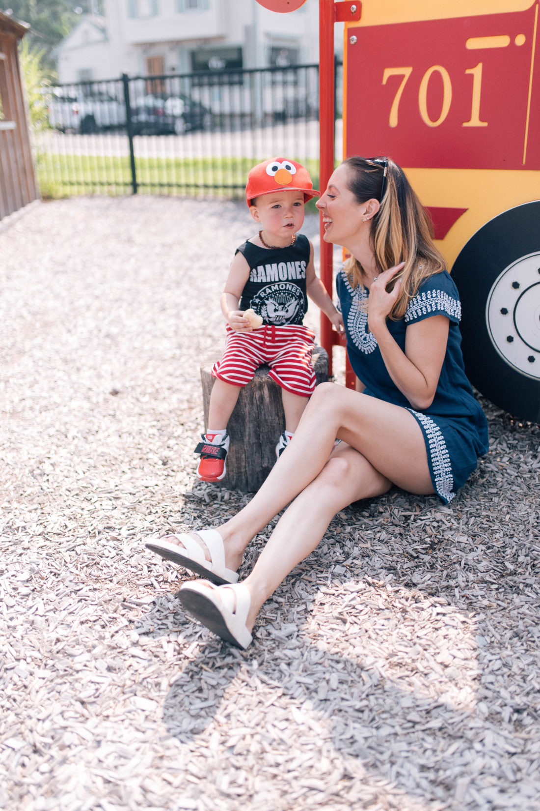 Eva Amurri Martino sits on the ground at the playground, and leans in to give her son a kiss on the cheek while he finishes his snack