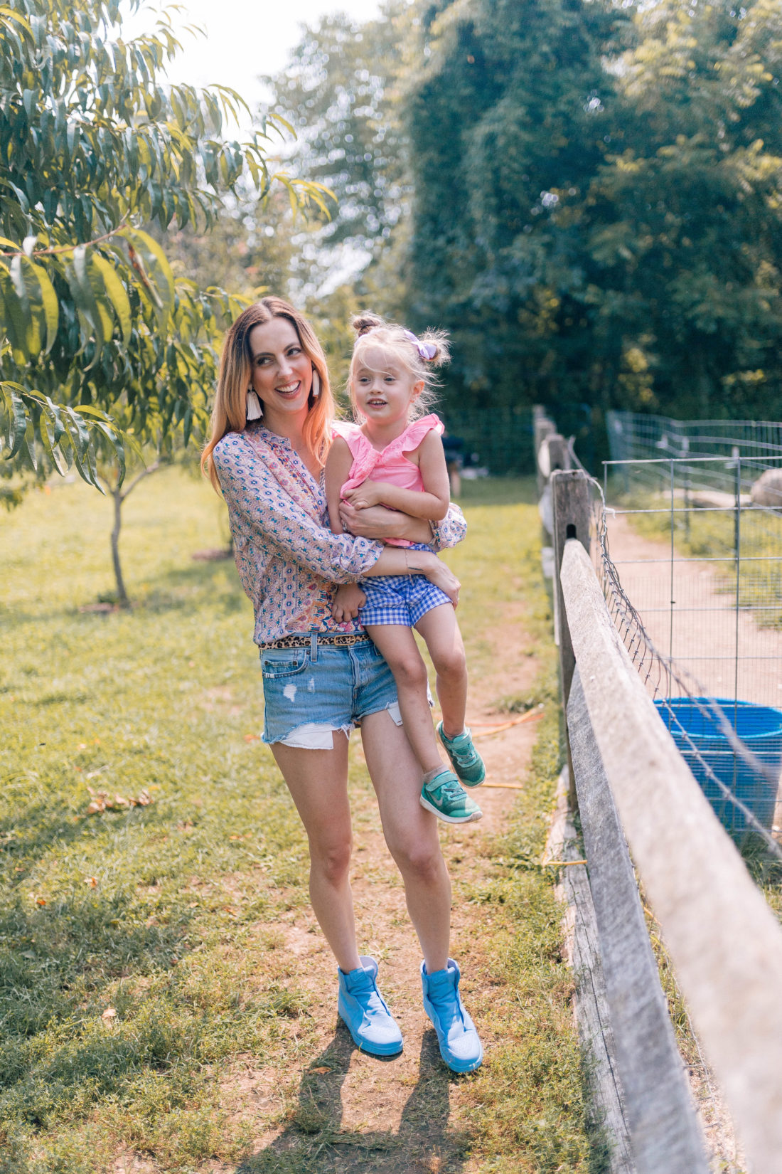 Eva Amurri Martino wears denim cutoffs and a silk shirt, and carries Marlowe Martino in her arms through the fields of a local connecticut farm