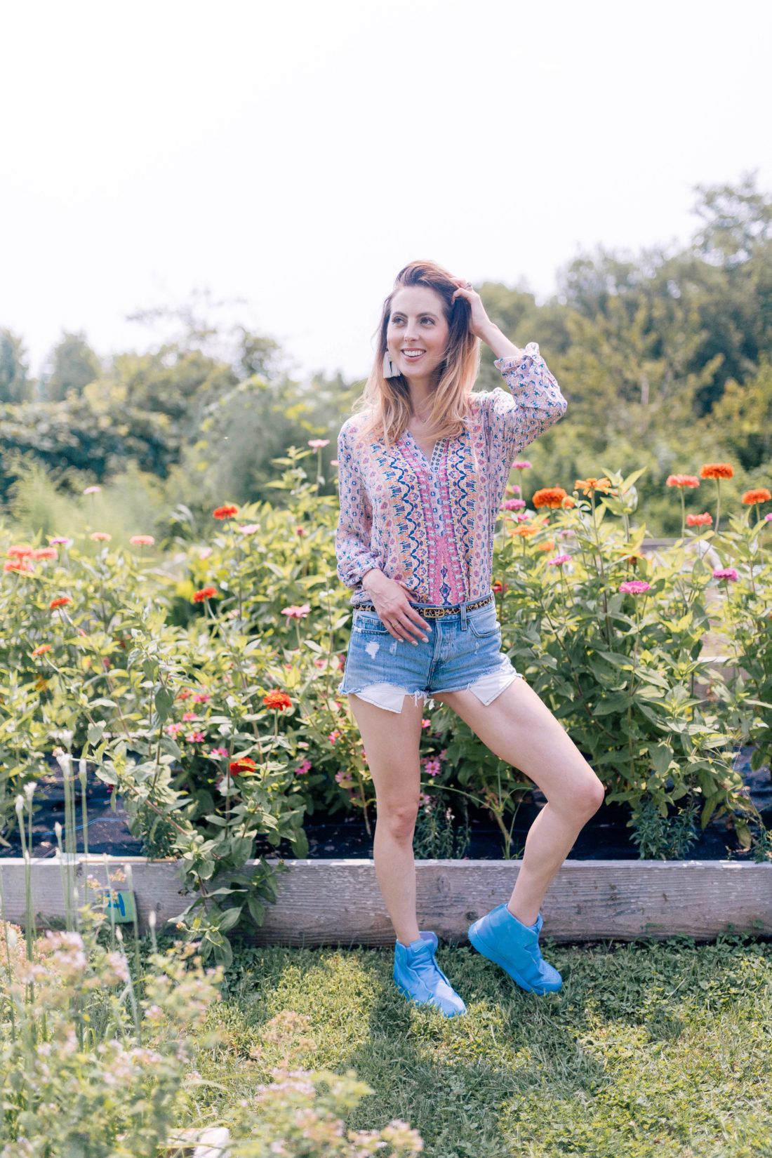 Eva Amurri Martino wears denim cutoffs and a printed top and stands in the garden of a local connecticut farm