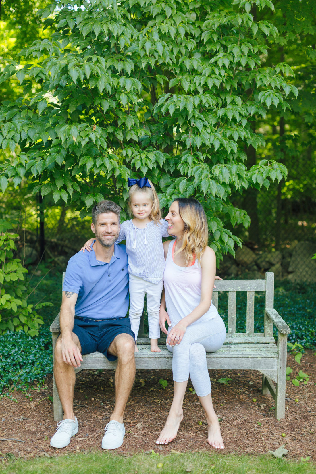Eva Amurri Martino and Kyle Martino sit with four year old daughter marlowe on a bench surrounded by greenery in the yard of their Connecticut home