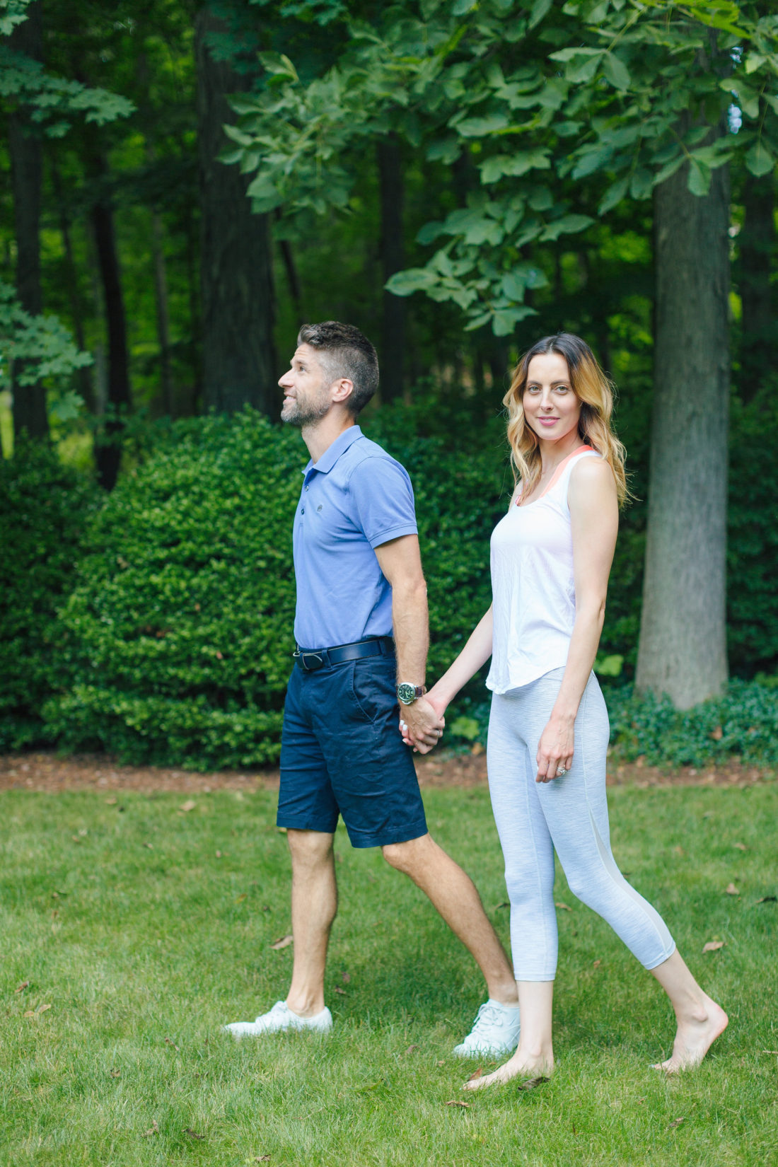 Eva Amurri Martino and Kyle Martino hold hands while wearing active wear, and strolling through the grounds of their Connecticut home