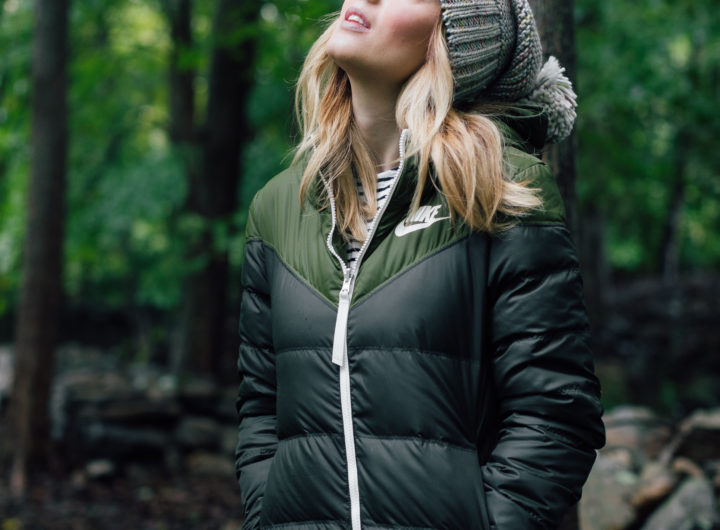Eva Amurri Martino wears a puffy jacket and a grey knit hat and stands in the woods in Connecticut