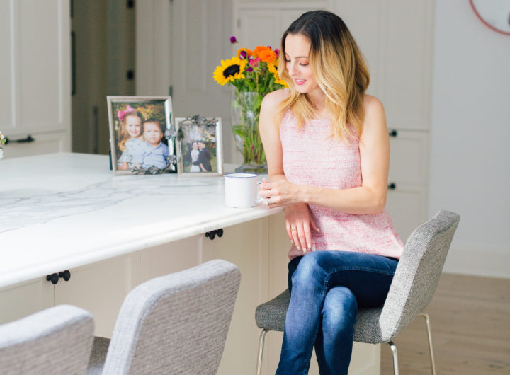 Eva Amurri Martino wears denim and a knit top, and sits at the marble island in the kitchen of her Connecticut home