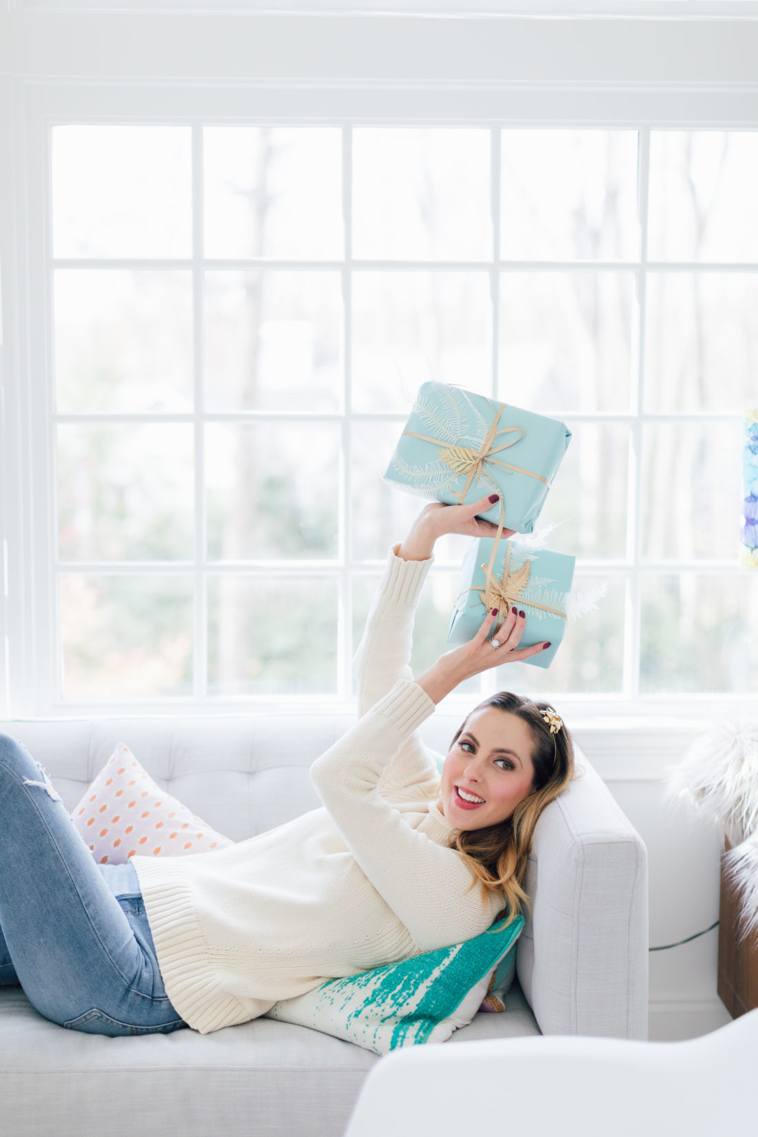 Eva Amurri Martino wears her cream colored sweater and levi jeans, and lays on the couch at home, holding robin's egg colored gifts with gold ribbon