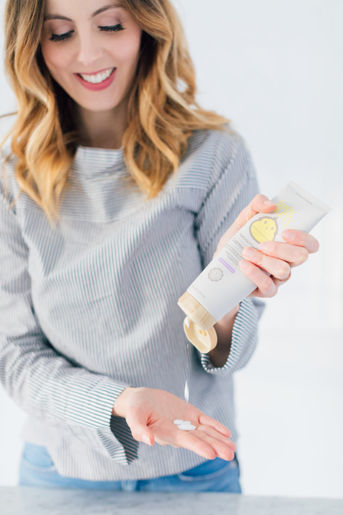 Eva Amurri Martino wears a striped boatneck top, and squeezes all natural lotion in to her hand