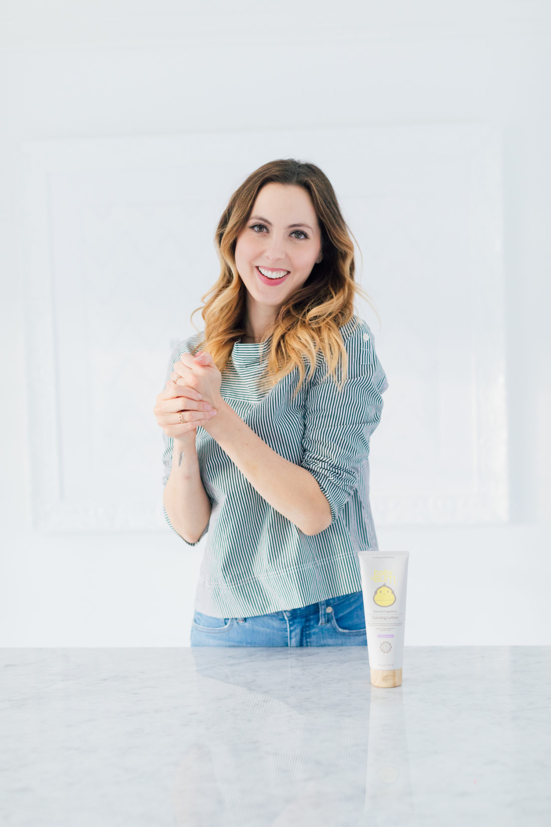 Eva Amurri Martino wears a striped boatneck top, and uses baby bum calming lotion to moisturize her hands and arms