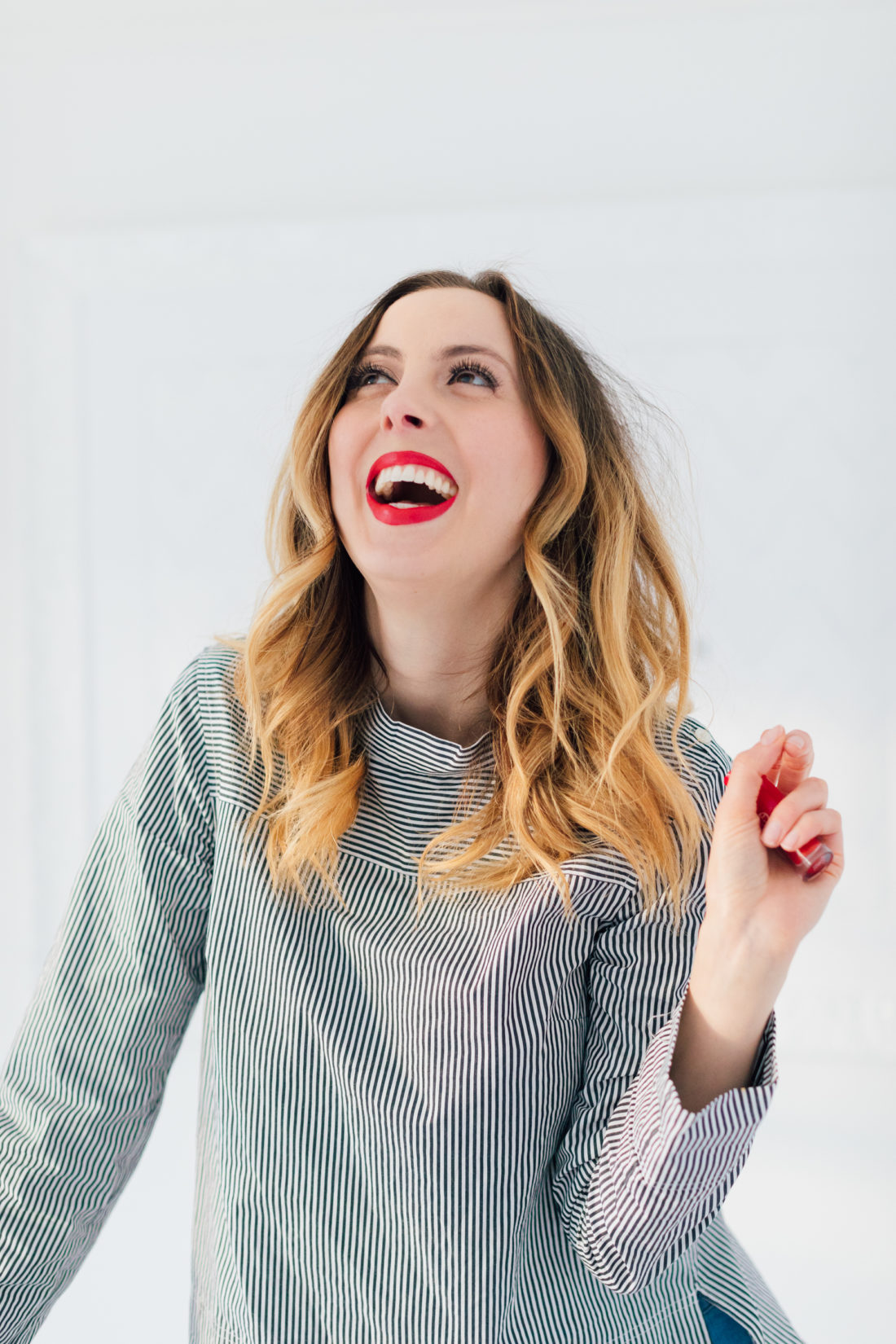Eva Amurri Martino wears a striped boatneck top, and the perfect holiday red shade of lipstick