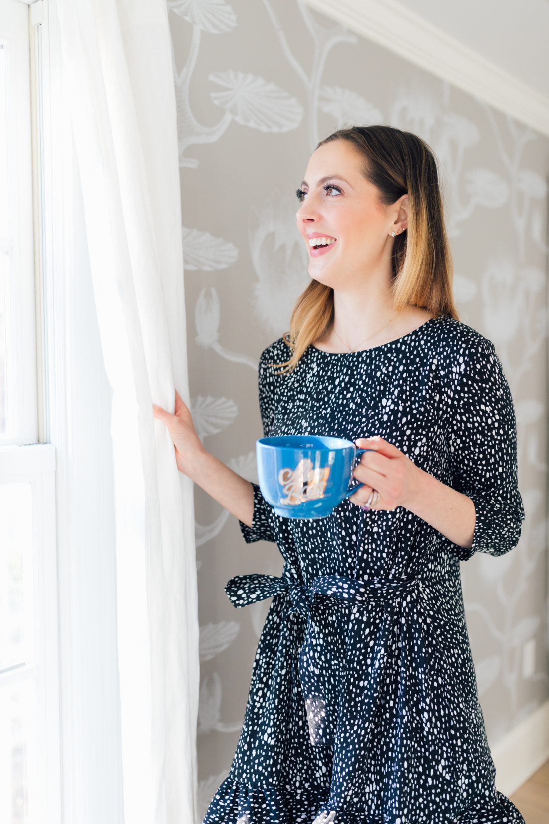 Eva Amurri Martino wears a ruffled printed dress and holds a blue mug while she peers out of the curtains in the bright and airy dining room in her Connecticut home