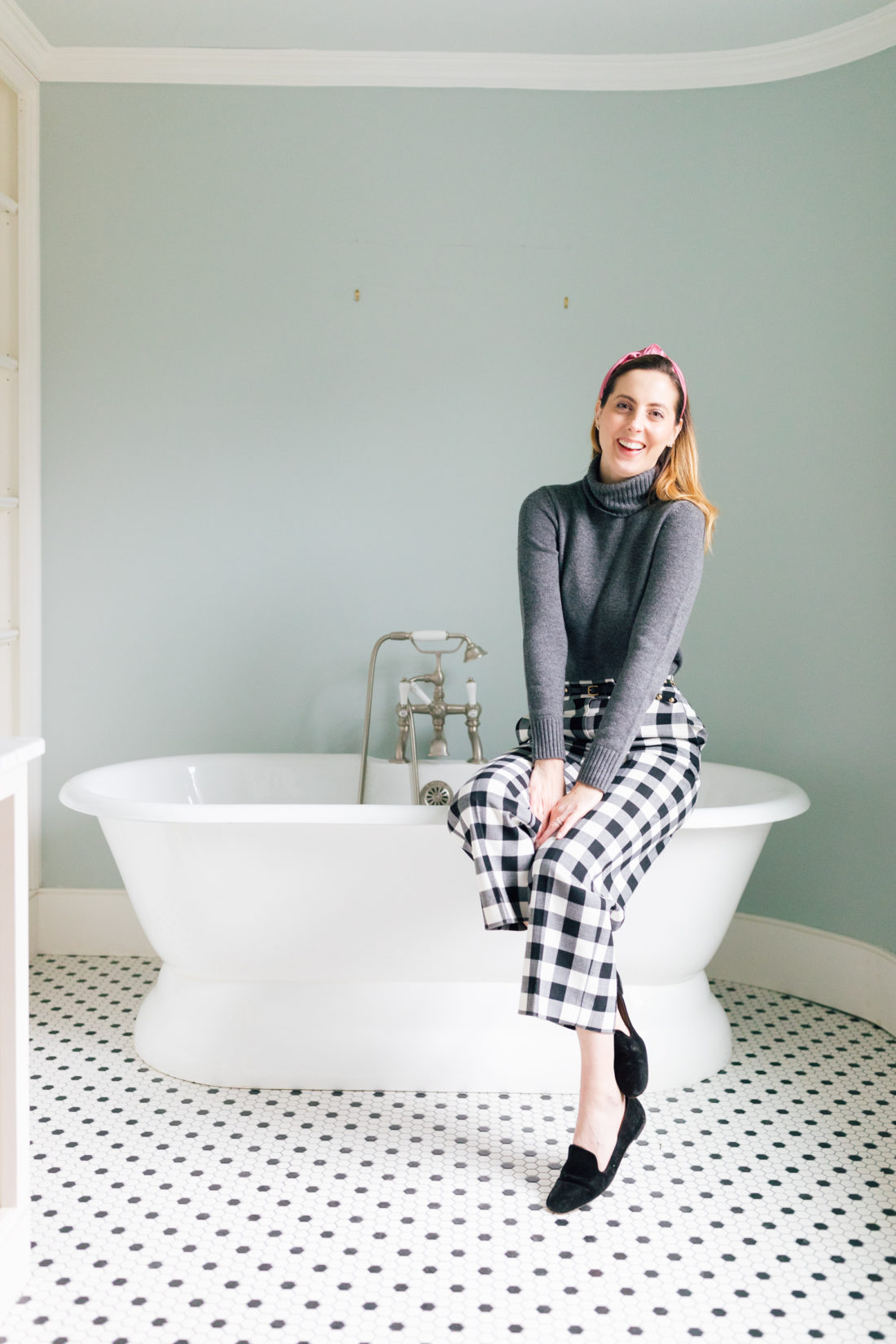 Eva Amurri Martino sits on the edge of a bathtub in the bathroom of her new home before renovations