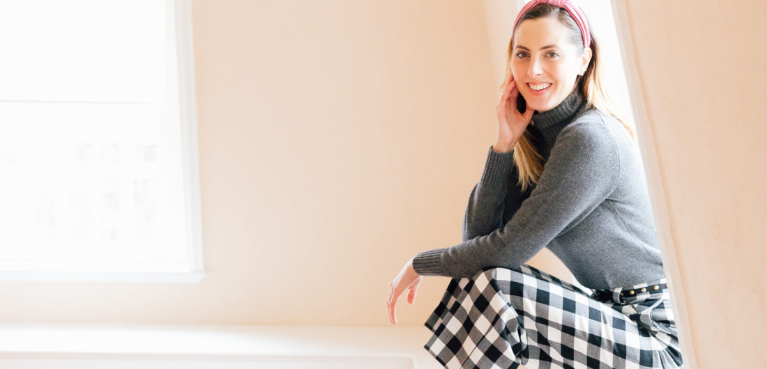 Eva Amurri Martino wears checked trousers and a grey cashmere sweater, and sits in her empty home that awaits renovations