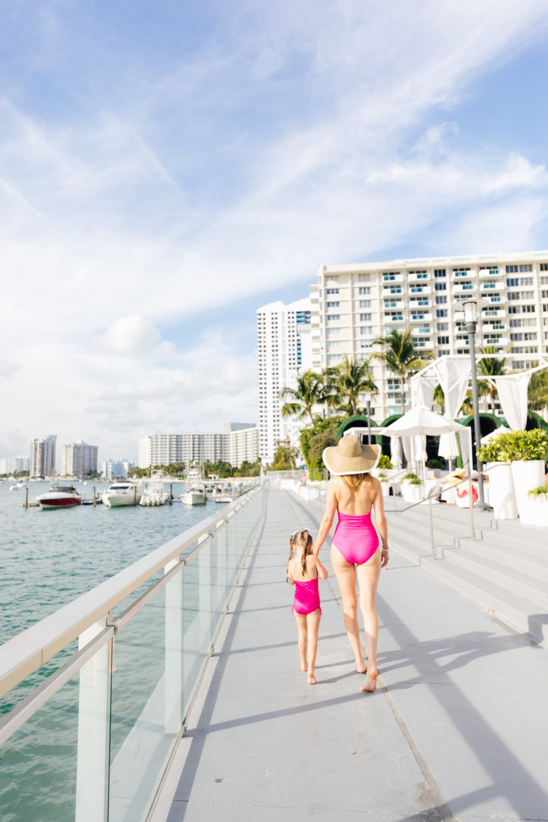 Eva Amurri Martino and Marlowe Martino walk along the edge of the water wearing matchig fuschia and gold bathing suits from the HEA x masala Baby capsule collection