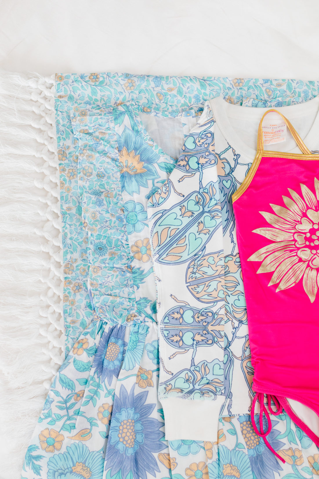 The Happily Eva After x Masala Baby resort capsule collection is layed out on a white background with an array of patterns in blue tones and a pop of color in the bright fuschia bathing suit