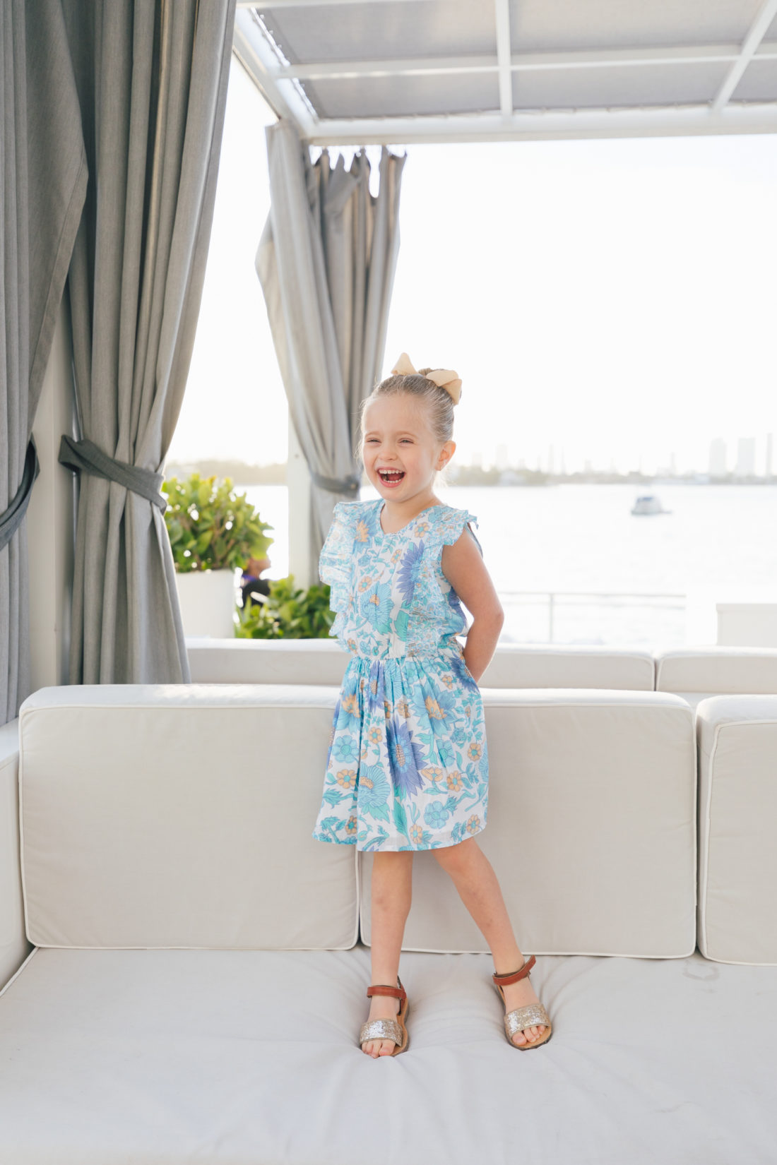 Marlowe Martino laughs while standing in Miami wearing the fantasia dress from the Happily Eva After x Masala Baby capsule collection