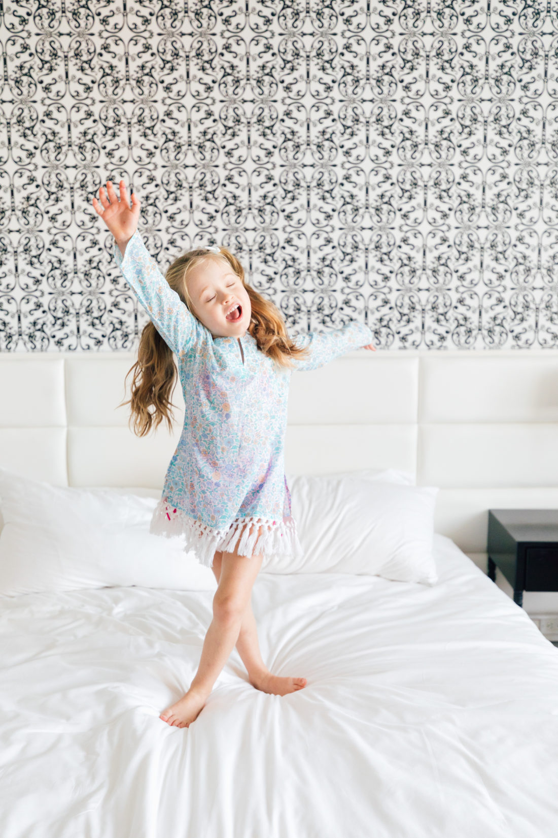 Marlowe Martino poses in her blue floral fringe tunic from the Happily Eva After x Masala Baby collection in a hotel room in Miami