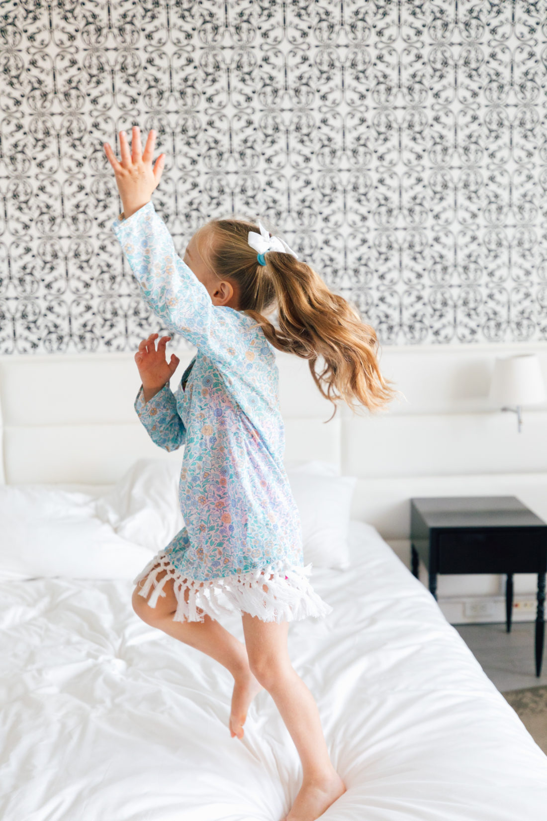 Marlowe Martino jumps and twirls on the bed in Miami wearing her Happily Eva After x Masala Baby floral fringe tunic