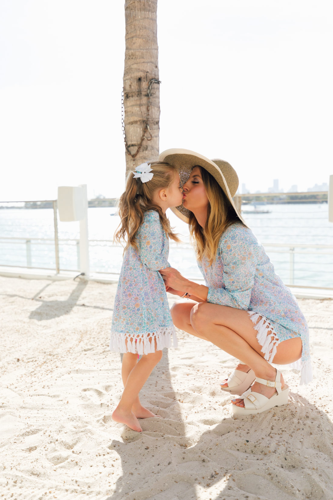 Eva Amurri Martino shares a sweet kiss with daughter Marlowe Martino on the beach in Miami while wearing their matching Mother daughter fringe tunics from the Happily Eva After x Masala Baby collection