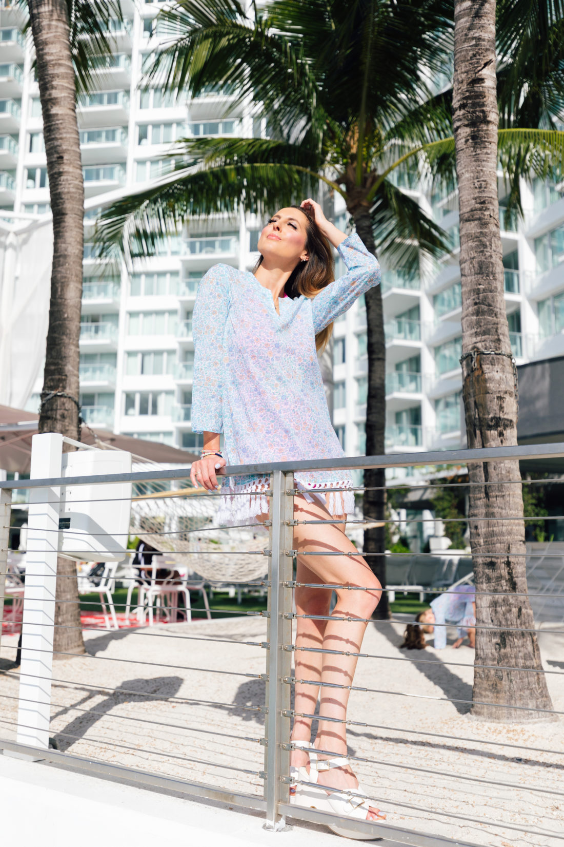 Eva Amurri Martino wears her Happily Eva After x Masala Baby floral fringe tunic and basks in the sun in front of her hotel in Miami