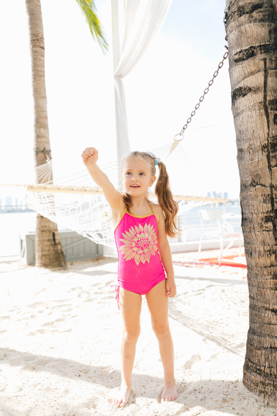 Marlowe Martino wears a pink and gold floral bathing suit on the beach in miami as part of the Happily Eva After x Masala Baby lookbook