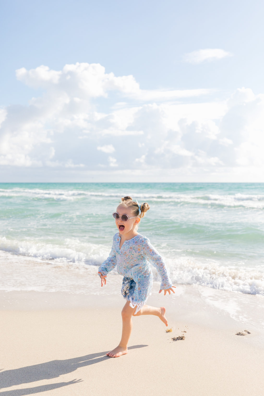 Marlowe Martino wears a blue, floral tunic from the Happily Eva After x Masala Baby capsule collection, and denim shorts, and frolics in the sand and surf beachside in Miami