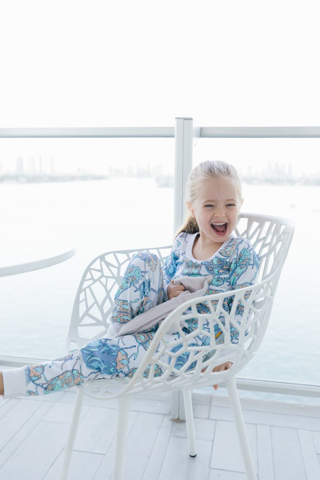 Marlowe Martino relaxes on the balcony in Miami wearing her buggy pajamas from the Happily Eva After x Masala Baby capsule collection