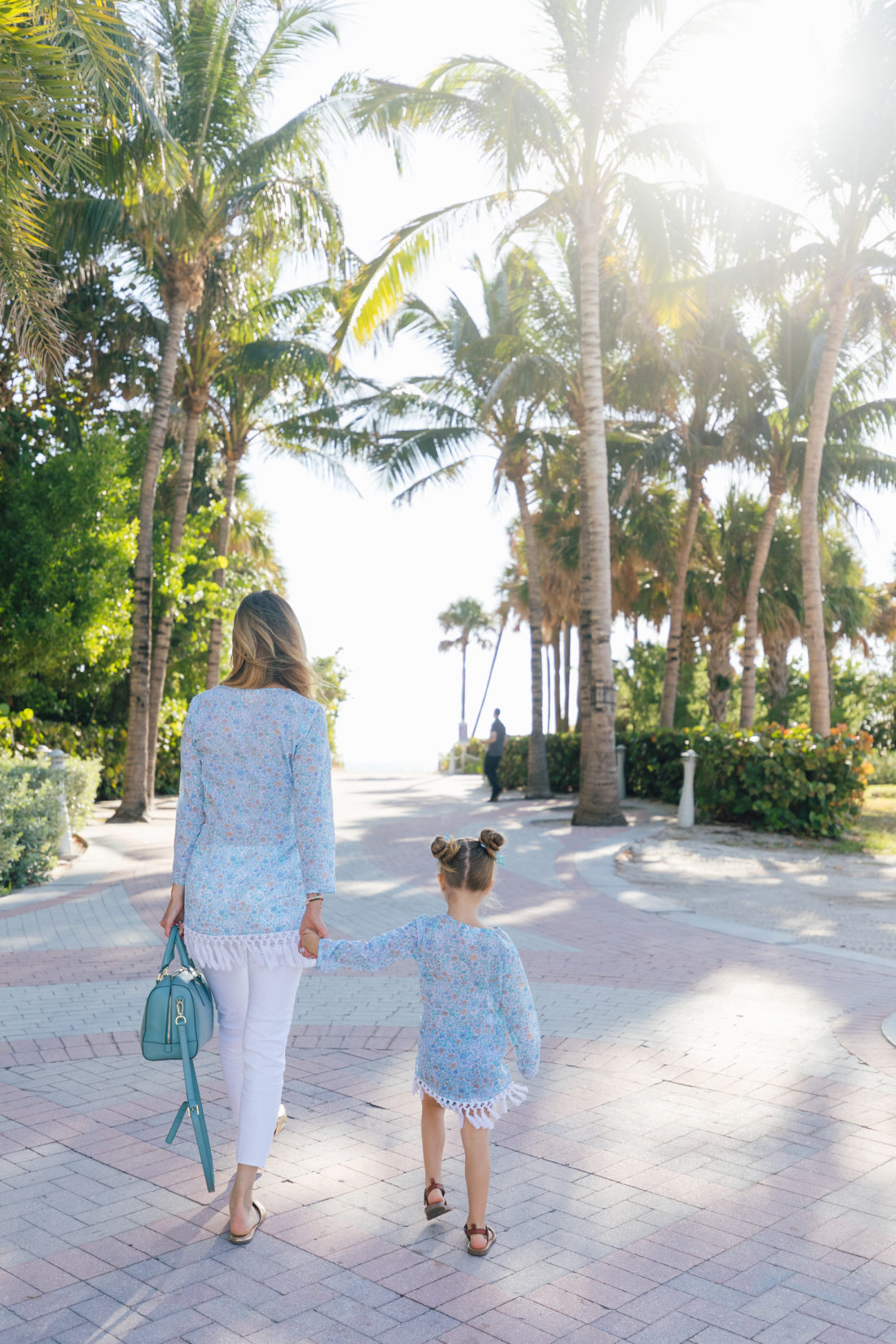 Eva Amurri Martino and Marlowe Martino walk together towards the beach in Miami wearing matching floral fringe tunics from the Happily. Eva After x Masala Baby capsule collection