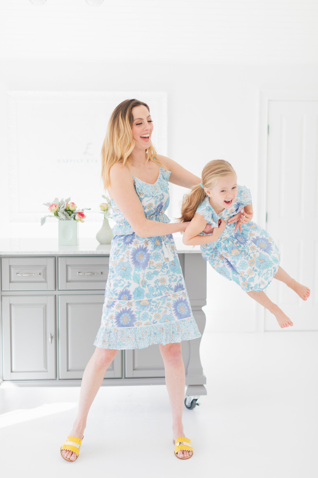 Eva Amurri Martino swings daughter Marlowe in her arms while wearing matching floral printed dresses from the Happily Eva After x Masala Baby capsule collection