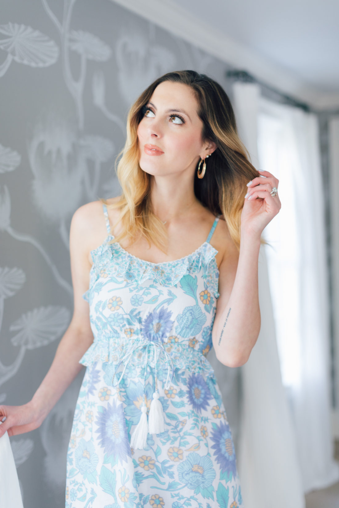 Eva Amurri Martino wears a floral dress from her Happily Eva After x Masala Baby Capsule collection in the dining room of her connecticut home