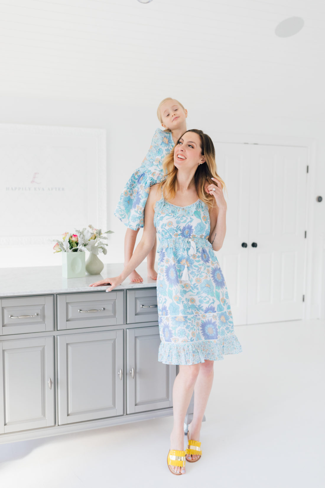 Eva Amurri Martino stands in a floral ruffle dress in the studio of her connecticut home with four year old daughter Marlowe