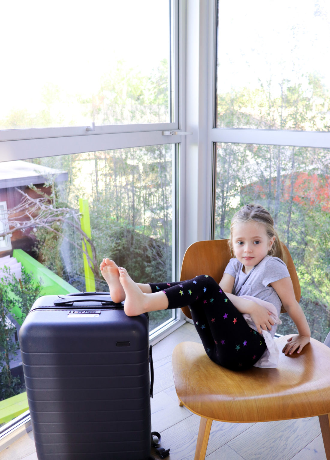 Marlowe Martino sits on a chair and rests her feet on a carry-on suitcase as part of a blog post about the best toddler travel tips