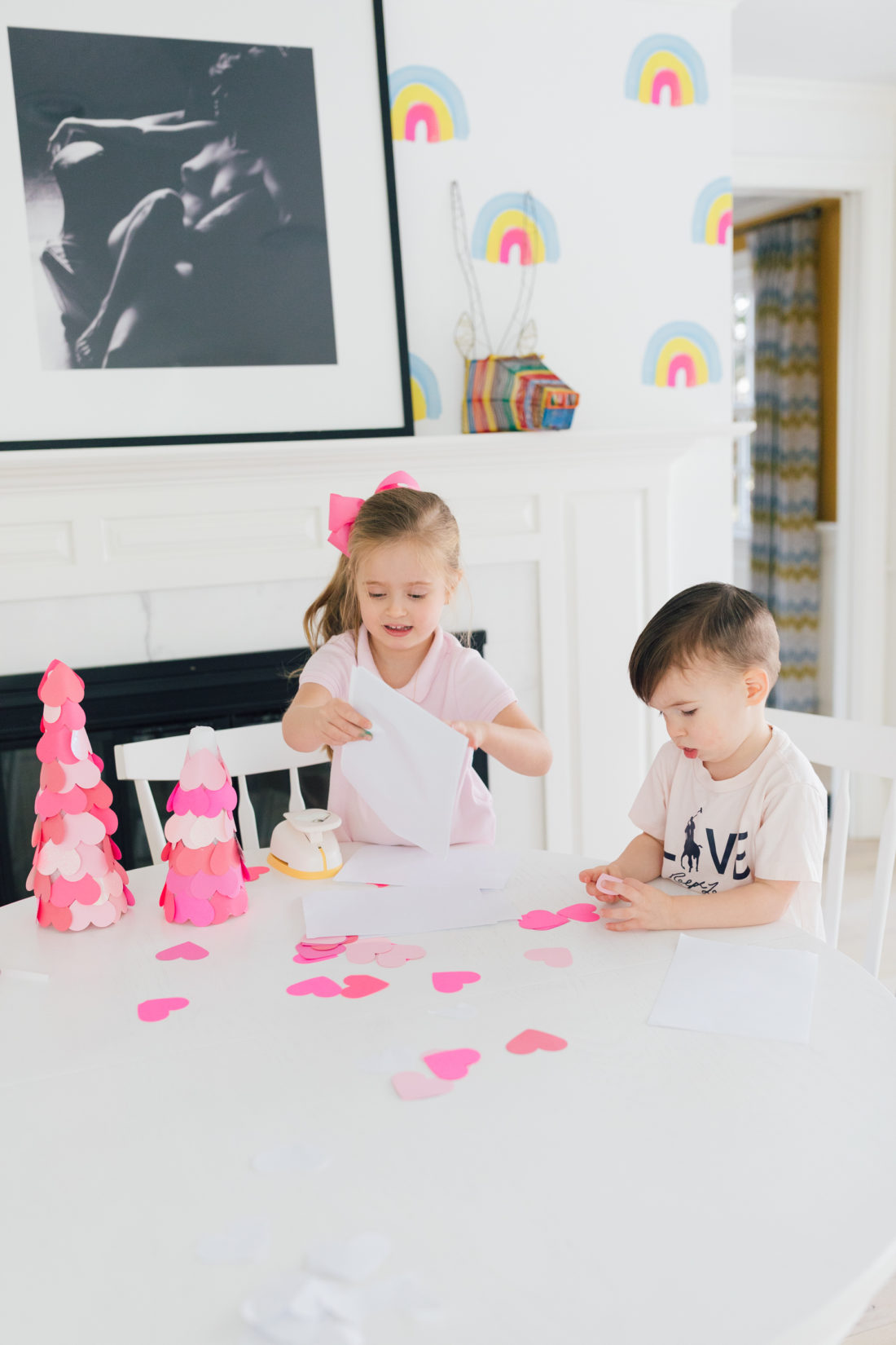 Marlowe and Major martino use a heart hole pumch to create the materials for a valentine's day craft