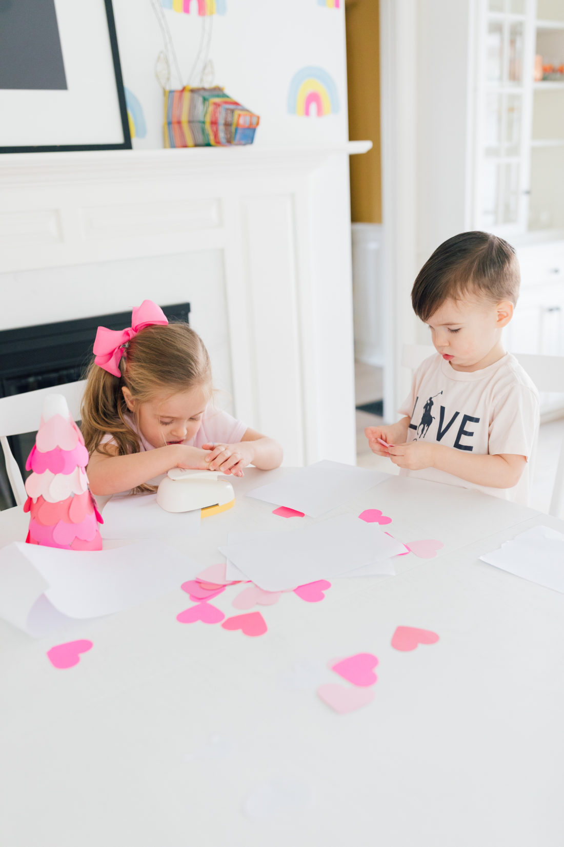 Marlowe and Major martino wear shades of pink and use a large heart hole punch to make materials for a Valentine's Day craft