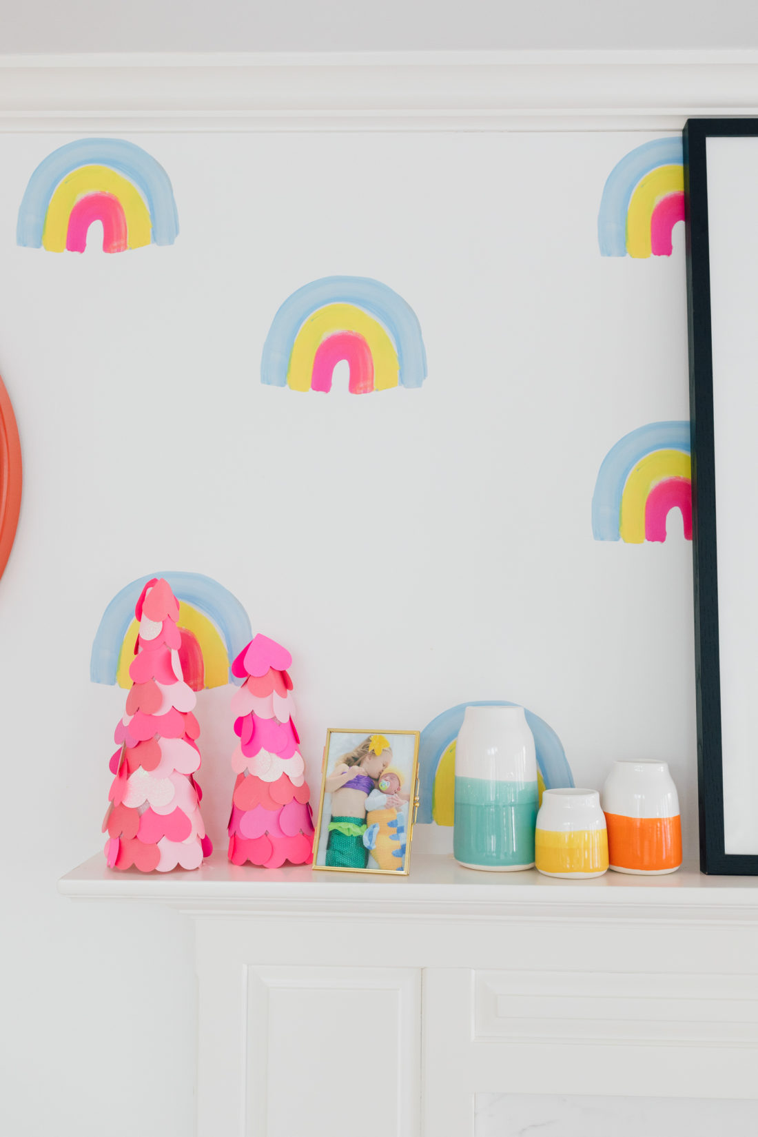 DIY ombre heart trees on display next to multicolored vases and rainbow decals on the mantle at Eva Amurri Martino's Connecticut home