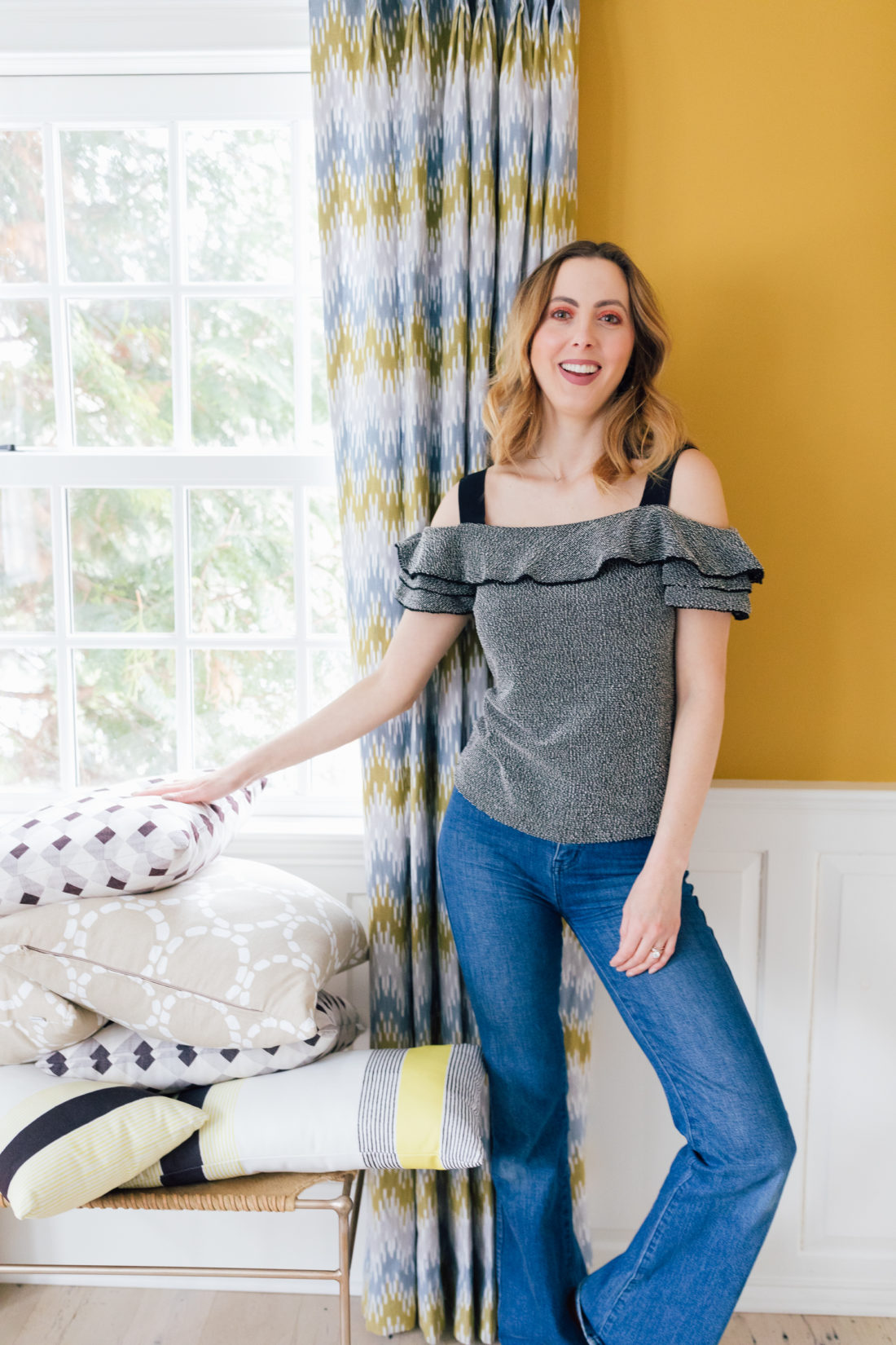 Eva Amurri Martino wears jeans and an off the shoulder top, and stands in the living room of her connecticut home as she prepares to move house