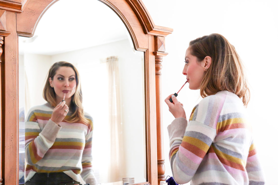 Eva Amurri Martino of Happily Eva After gets ready to begin her day by putting on lipgloss in the mirror.