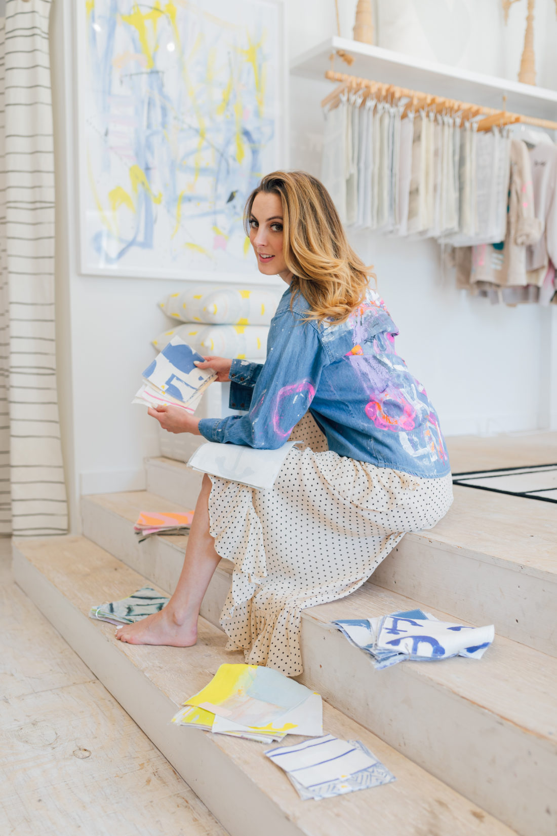 Eva Amurri Martino wears a painted Kerri Rosenthal denim jacket and peruses fabric and wallpaper samples for her home renovation