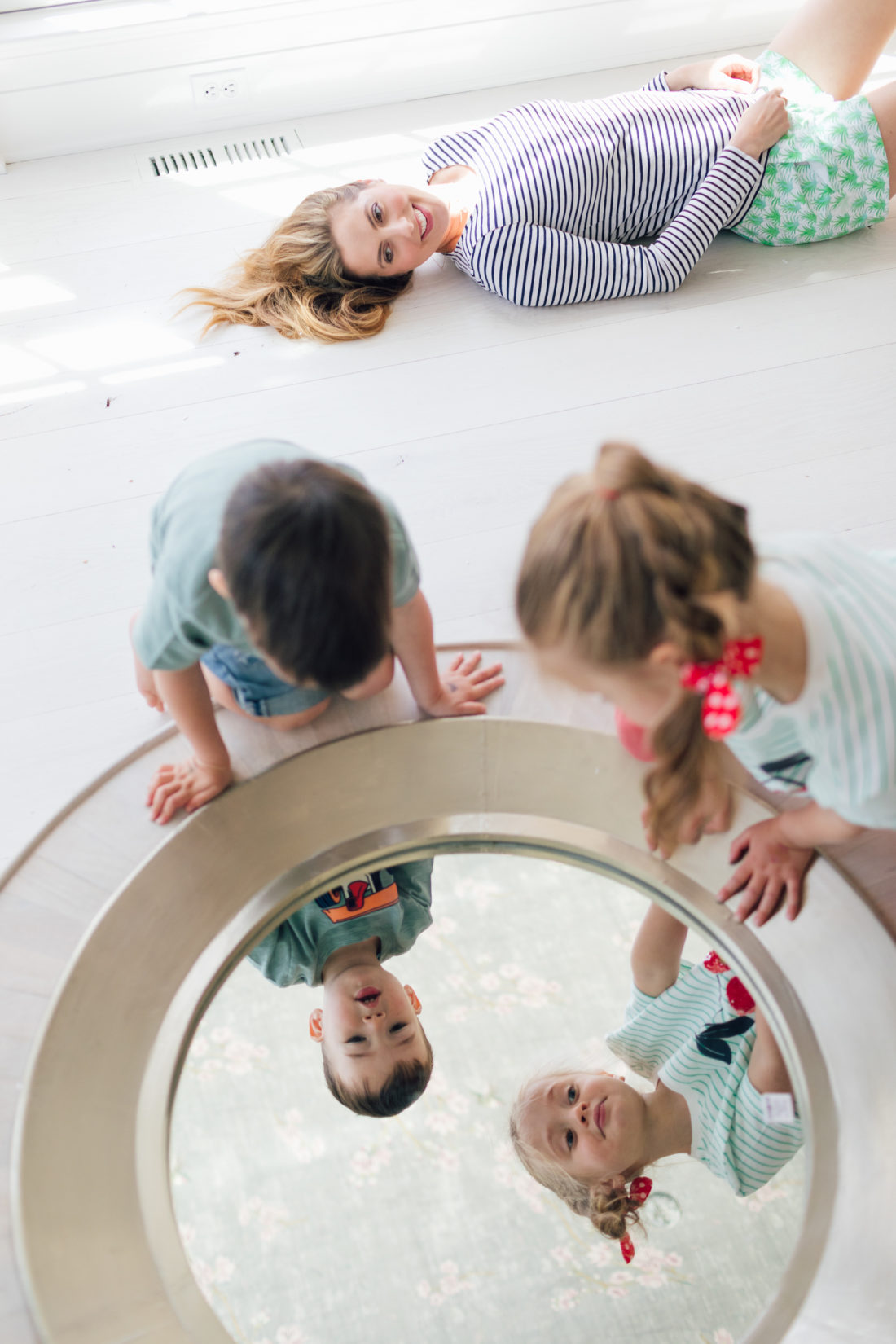 Eva Amurri Martino of Happily Eva After lies on the floor of her new house in Connecticut while her kids Marlowe and Major gaze into an unhung wall mirror