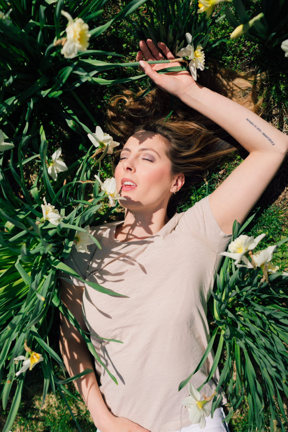 Eva Amurri Martino of Happily Eva After lies in a pile of daffodils and shares her favorite nude colored pieces for spring