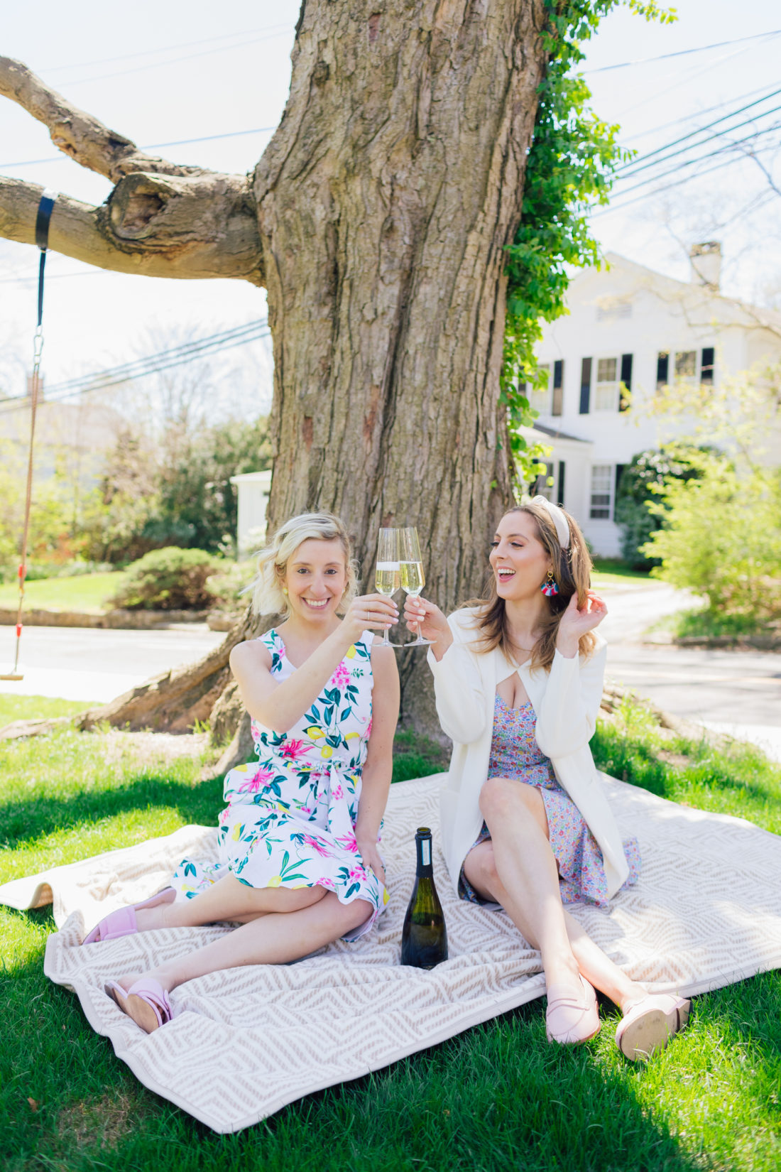 Eva Amurri Martino of Happily Eva After and Julia Dzafic of Lemon Stripes sit under a tree drinking champagne and reminiscing on their parenting style